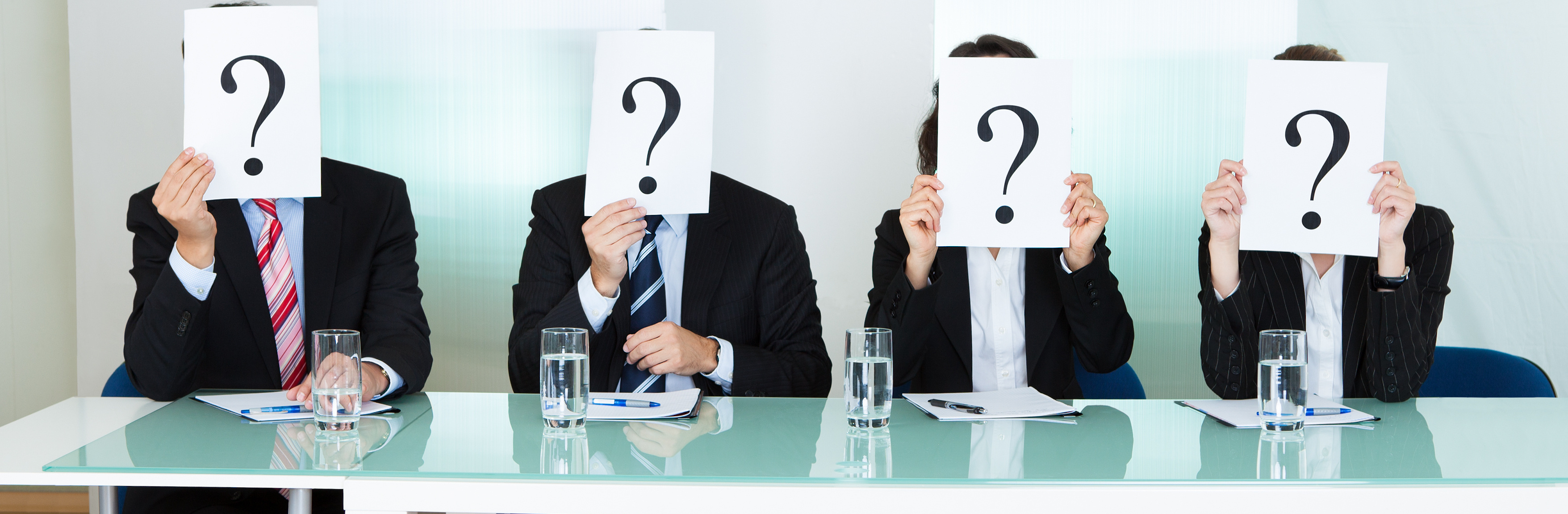 Row of businesspeople with question marks signs in front of their faces